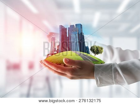 Closeup Of Business Woman In Shirt Keeping Green Island With Skycraper City In Her Hands With Office