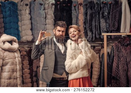 Expensive Clothes And Money Concept. Couple Shopping In Fur Mall. Woman In White Fur Coat With Beard