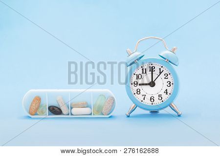 Pills And Capsules In Organizer And Clock On Blue Background. Time To Get Healthy, Daily Vitamins An
