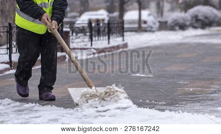 Man With Snow Shovel Cleans Sidewalks In Winter.