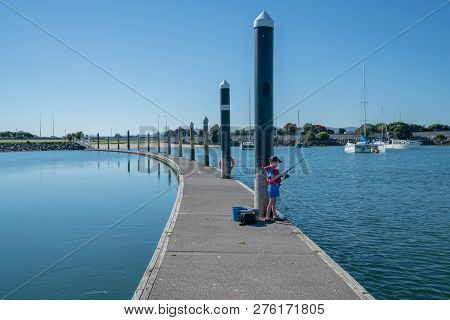 Small Boy On Pier Dividing Image And Calm From Rippled Water In Red Life Jacket Fishing From Pier Of