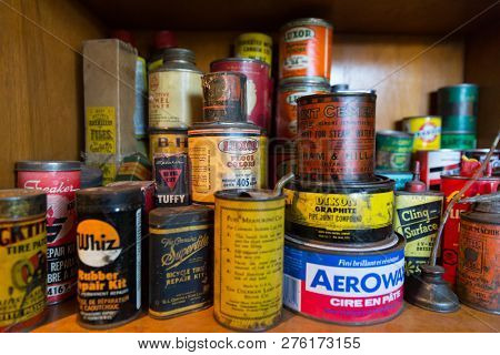 Quebec Province, Canada - 25th January 2015: A stack of old product tins for sale in a flea market, including motor products, paints, household repairs and cleaning agents