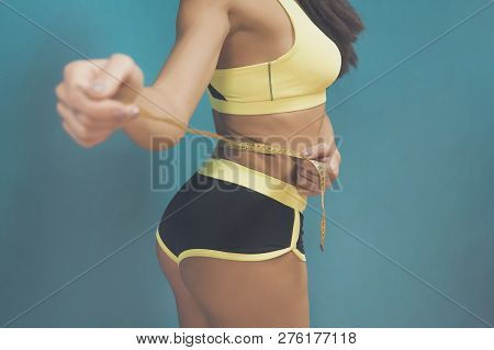 Cropped Shot Of Girl In Sportswear Measuring Herself With Metric Tape At Blue Background. Girl In Sp