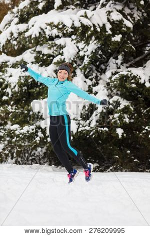 Winter Fun People Concept. Young Girl Jumping In The Snow. Attractive Lady Wearing Blue Jumper And S