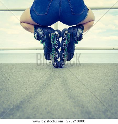 Back View Of Unrecognizable Woman Buttocks Wearing Short Blue Jeans Shorts And Roller Skates Enjoyin