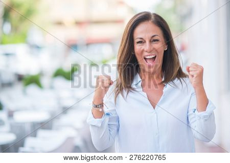 Beautiful middle age hispanic woman at the city street on a sunny day screaming proud and celebrating victory and success very excited, cheering emotion