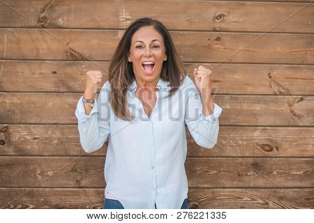 Beautiful middle age hispanic woman at over wood wall on a sunny day screaming proud and celebrating victory and success very excited, cheering emotion