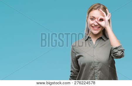 Young blonde business woman over isolated background doing ok gesture with hand smiling, eye looking through fingers with happy face.