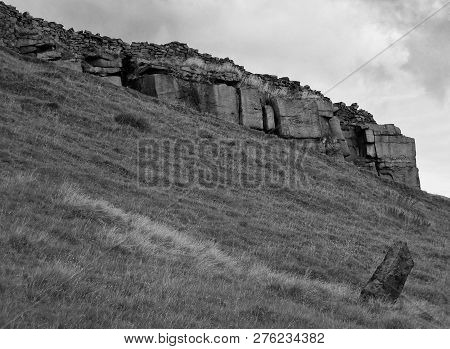 A Monochrome Image Of A Large Stone Outcrop With Round Stone Wall On A Hillside With A Standing Ston