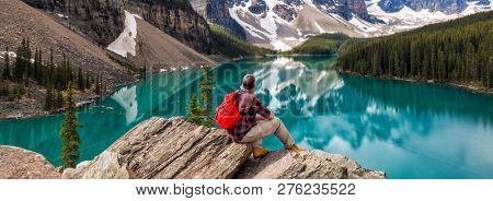 Panoramic web banner hiking man sitting down with rucksack backpack standing on tree log by Moraine Lake looking at snow covered Rocky Mountain peaks, Banff National Park, Alberta Canada