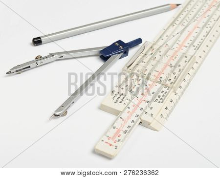 Logarithmic Ruler, Compasses, Pencil On A White Background . Stationery For Engineers And Students.