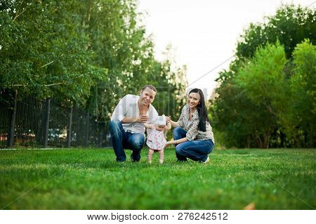 Happy Family Mother, Father, Child Daughter. Happy Young Family Spending Time Together Outside In Gr