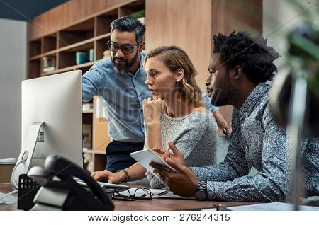 Focused businesspeople discussing project while looking at computer screen. Mature manager working with his creative team in a modern office. Multiethnic casual teamwork at work.