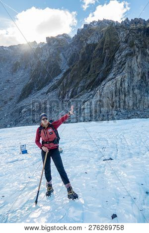 New Zealand, South Island, Fox Glacier - May 2016: An Unidentified Tour Guide Points To The Top Of T