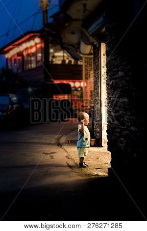 Taiwan, Taipei, Jiufen - May 2013: An Unidentified Young Boy Curiously Looks Into A Stall On Street