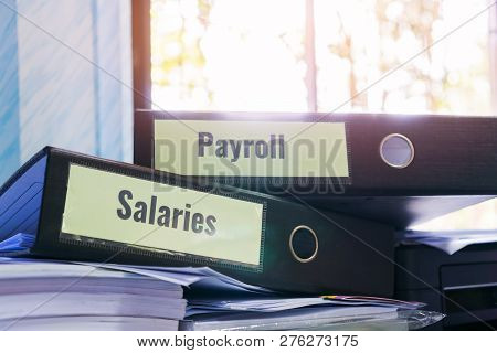 Payroll And Salaries Folders Stack With Label On Black Binder On Paperwork Documents Summary Report,