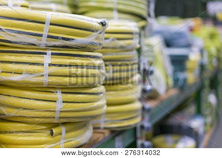 Stacks Of Rolls Yellow Pvc Plastic Pipe On The Counter In The Store. Sale Hoses In The Garden Of Var