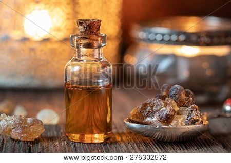 A Bottle Of Essential Oil With Frankincense Resin Crystals