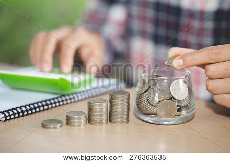 Business Accounting With Saving Money With Hand Putting Coins In Jug Glass, Businessman Writing Fina