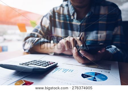 Businessman Or Accountant Working On Calculator To Calculate Business Data, Accountancy Document And