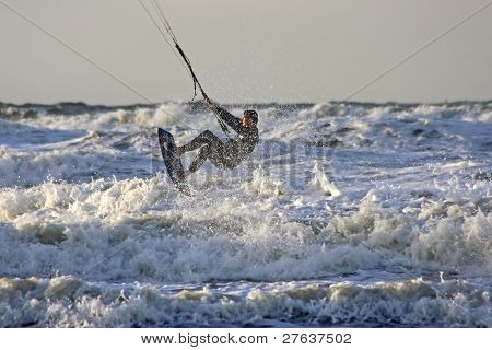 Kite surfer jumping on the waves at the north sea coast in the Netherlands