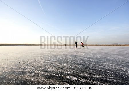 Ice skating on a wide open lake in the countryside in the Netherlands