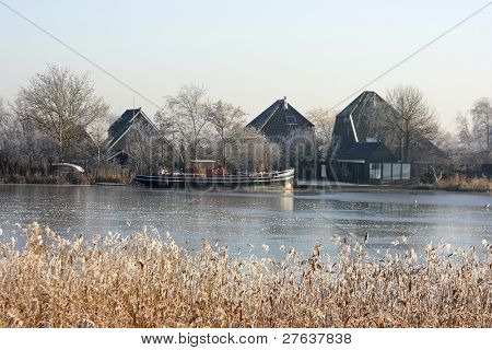 Cold winterday in Holland with frozen boat in a frozen icy canal in the countryside