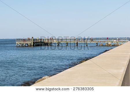 Hampton, Virginia - July 9, 2017:  People Fish On Engineer Pier Along The Chesapeake Bay At Fort Mon