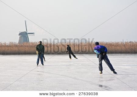Typically dutch: ice skating on a frozen lake with view on a windmill on a cold winterday