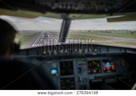 Pilot's view from a commercial airliner airplane flight cockpit during approach/landing