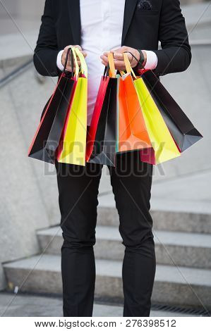 Man Carries Shopping Bags Urban Background. Successful Businessman Shopping Online. Busy People Appr