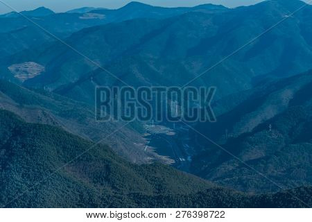 Highway In Valley Surrounded By Mountains With Power Line Towers Dissecting The Image Taken On Hazy