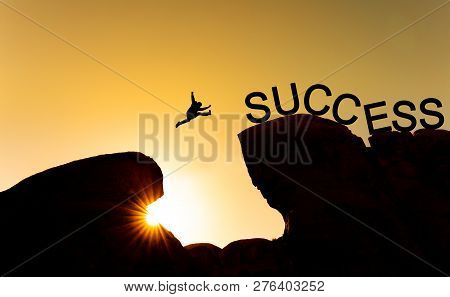 Business Success, Challenge, Achievement And Leadership Concept. Silhouette A Man Jumping Over Preci