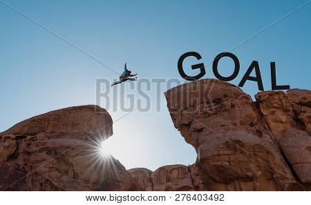 Goals Challenge, Achievement,risk And Success Concepts. Silhouette A Man Jumping Over Precipice