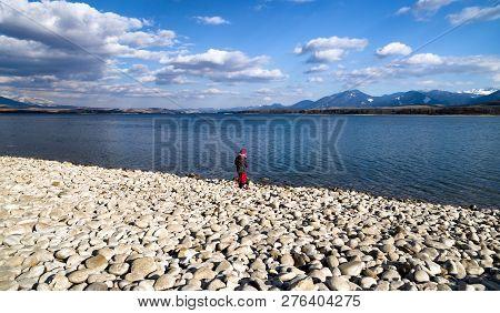 Lonely Little Kid Playing On The Shore Of Lake Liptovska Mara, Slovakia