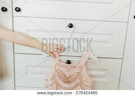 Hand Holding Beautiful Dressy Lush Pink Dress For Girls On Hanger At The Background Of White Wardrob