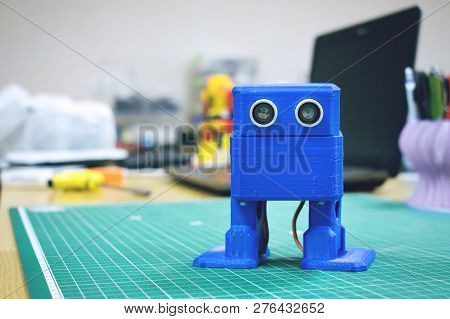 3d Printed Funny Dancing Blue Robot On The Background Of Devices And Laptop. Robot Model Printed On