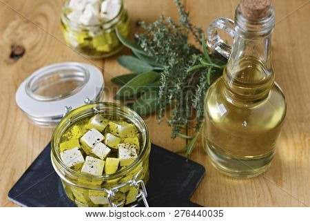 Marinated Feta In A Glass Jar, Spices And Olive Oil On A Wooden Background