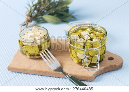 Marinated Feta In A Glass Jar And Spices Against Blue Background