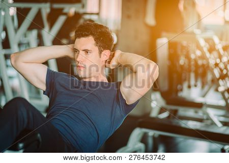 Fit Caucasian Handsome Man Sit Up On Machine In Sportswear. Young Man Sit Up Exercise To Strength Th