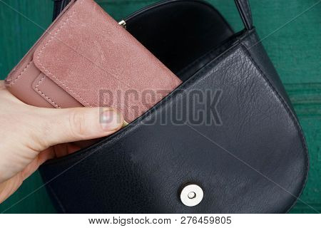 Hand Pulls Out A Brown Wallet From An Open Black Leather Bag