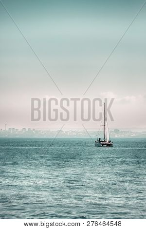 Sailing Boat With A White Sail On The Calm Sea. Cold Green Color
