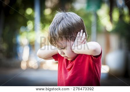 A 4 Year Old Autistic Child In A Red Shirt Closing His Ears With Hands As If Protecting From Noise.