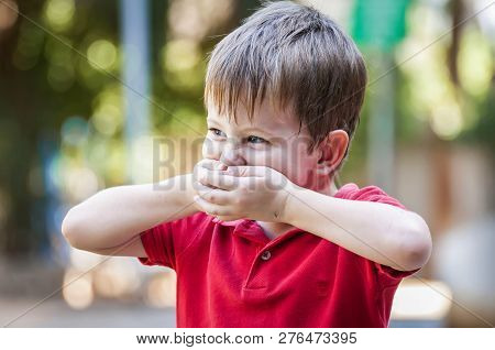 Funny Caucasian Child Closing His Mouth To Hide A Smile In The Park Outside In The Summer. Laughing