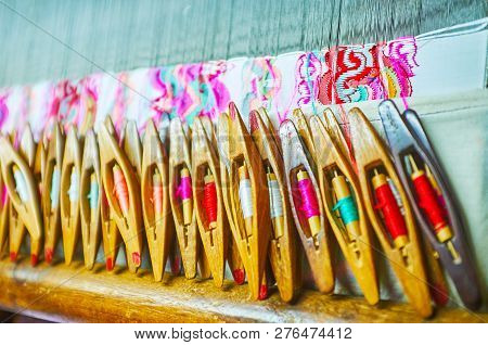 Multitude Of Old Wooden Weaving Flying Shuttles For The Handloom With Colorful Silk Weft Threads On