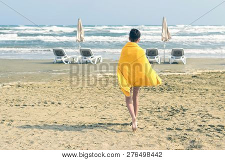 A Boy In A Yellow Towel Walks On The Sandy Mackenzie Beach In Larnaca In The Autumn Windy Weather. C