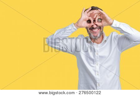 Handsome middle age elegant senior business man wearing glasses over isolated background doing ok gesture like binoculars sticking tongue out, eyes looking through fingers. Crazy expression.