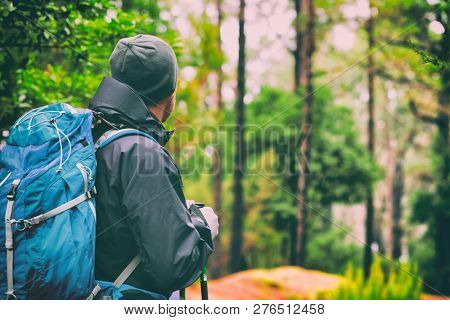 Travel hiking man hiker on trek hike with bag, hat, hiking poles. Active lifestyle people outdoor sports. Forest trail walking.