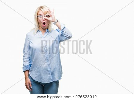 Young beautiful blonde business woman wearing glasses over isolated background doing ok gesture shocked with surprised face, eye looking through fingers. Unbelieving expression.