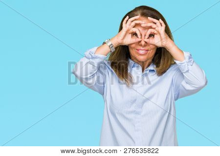 Beautiful middle age business adult woman over isolated background doing ok gesture like binoculars sticking tongue out, eyes looking through fingers. Crazy expression.